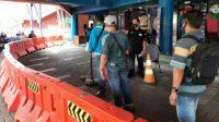 Masyarakat wajib pajak menjaga jarak dan diukur suhu tubuhnya oleh petugas saat akan memasuki kantor pelayanan Samsat Jakarta Timur. Foto: dok pribadi